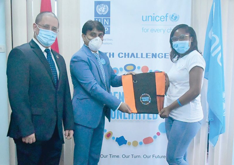 UNICEF's Country Representative, Irfan Akhtar hands over a Generation Unlimited token to Delecia Fraser of Team 'Youths with Purpose'. At left is UNDP's Resident Representative, Jairo Valverde Bermudez