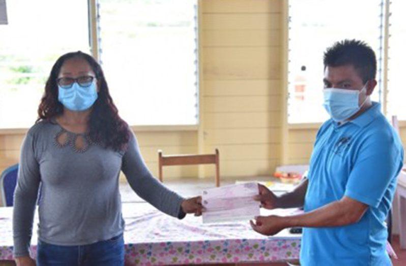 Amerindian Affairs Minister, Pauline Sukhai, hands over a cheque to Toshao of Phillipai, Mark Joseph (DPI photo)