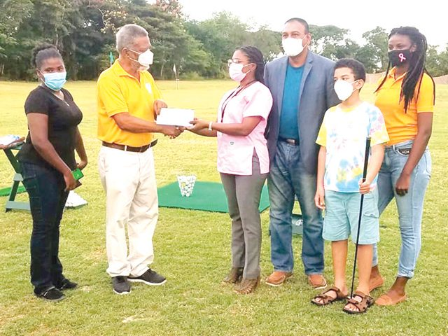 winner of the Women's Amateur division Leota King, ex-Prime Minister Sam Hinds hands over the check to Ms. Monette Harry of the Guyana Cancer Institute , Marcus Hinds Jr., GGA President Aleem Hussain