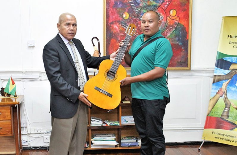 Minister Norton presenting the brand new guitar to Mr. Ishmael Abrams, a Councillor attached to the Regional Democratic Council of Region Seven