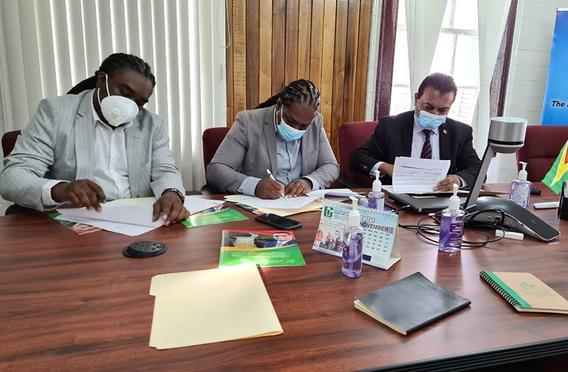 Principals of the H-Towers Luxury Hotel, Rawle Ferguson and Kerwin Bollers, signing the MoU with CEO of the Guyana Office for Invest, Dr. Peter Ramsaroop