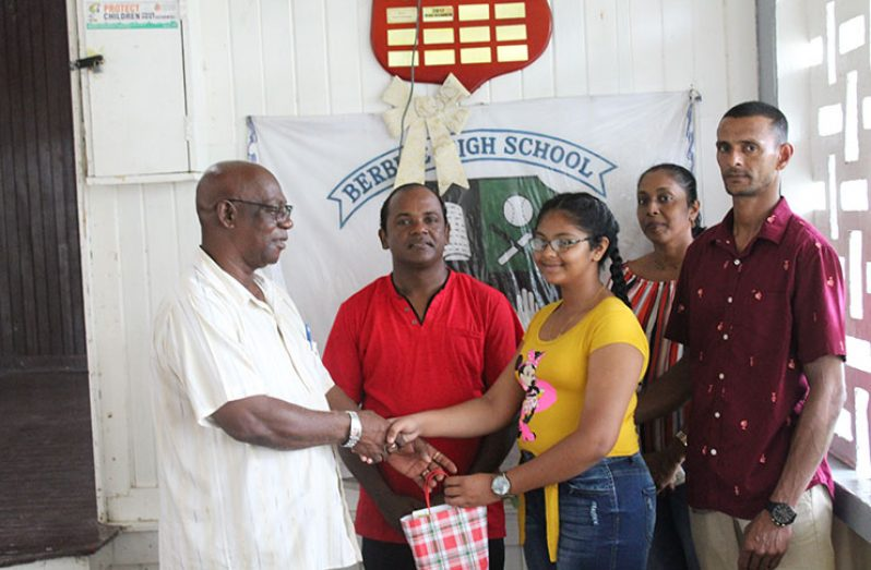 Chitra Ramdihal collecting her gift from NICIL Rose Hall's Mr. Anderson, while her Deputy headteacher, Mr. Basodeo Utam and her parents happily look on