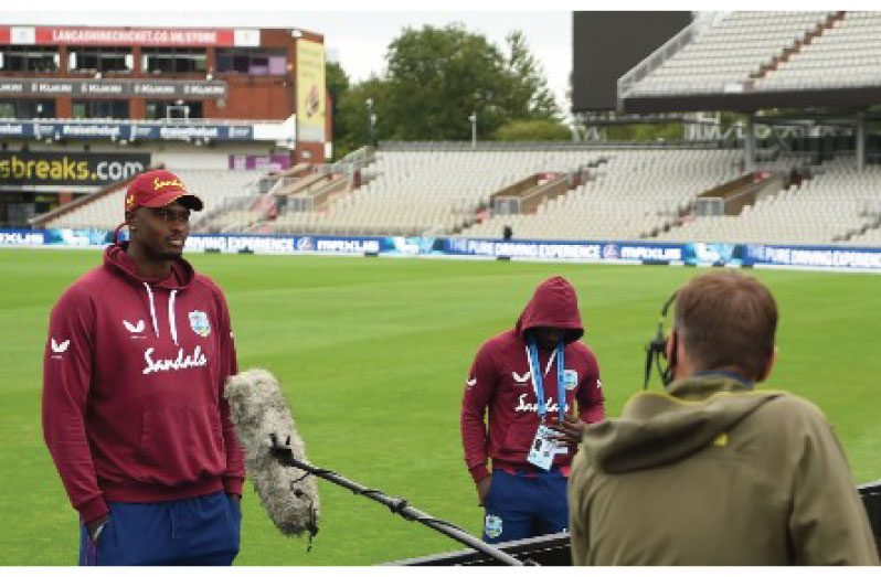 Captain Jason Holder (left) conducts a media interview at Old Trafford using social distancing.