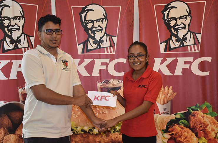 Russell Jubeer (left) receives the sponsorship from KFC's Senior Accounts Clerk, Oma.
