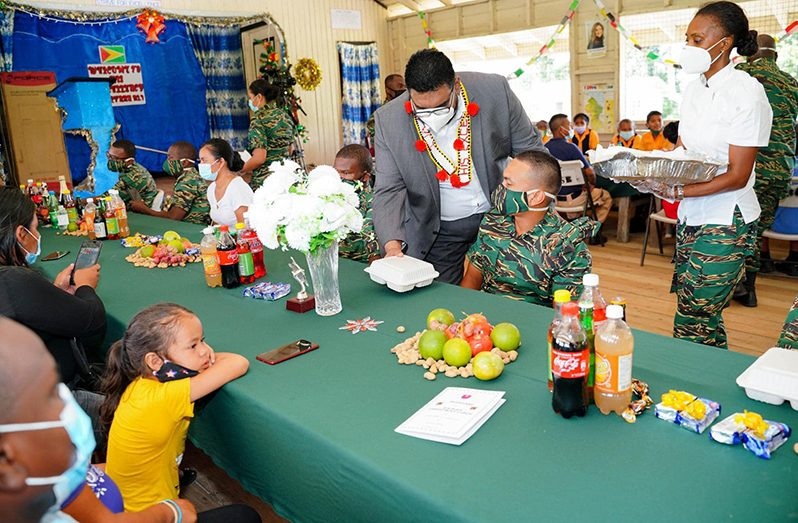 President Irfaan Ali serves a Guyana Defence Force rank who is stationed at Kaikan, Region Seven (Office of the President photo)