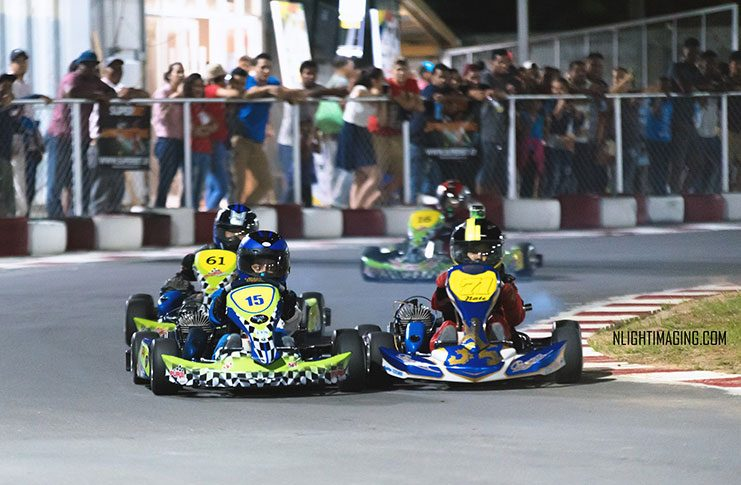Wheel-to-wheel action as Paige Mendonca (kart 15) leads Nathan Rahaman (71) during the Sunburst 60cc Kids Cup at the Georgetown Grand Prix last Friday.  (NLightimaging photo)