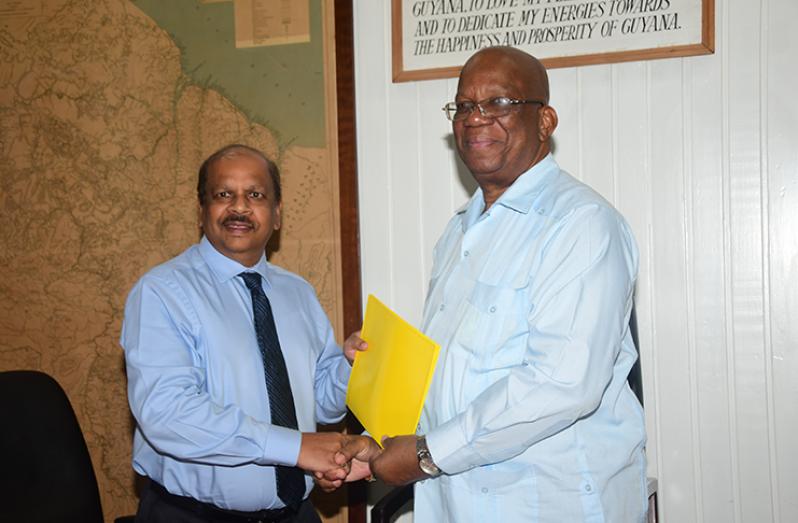 Minister of Finance, Winston Jordan hands over the signed agreement to Governor of BOG, Dr. Gobind Ganga (Adrian Narine photo)