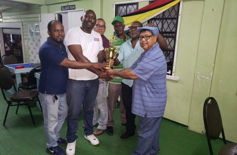 Manniram Shew hands over the winners' trophy to Keith Riley in the presence of his teammates.