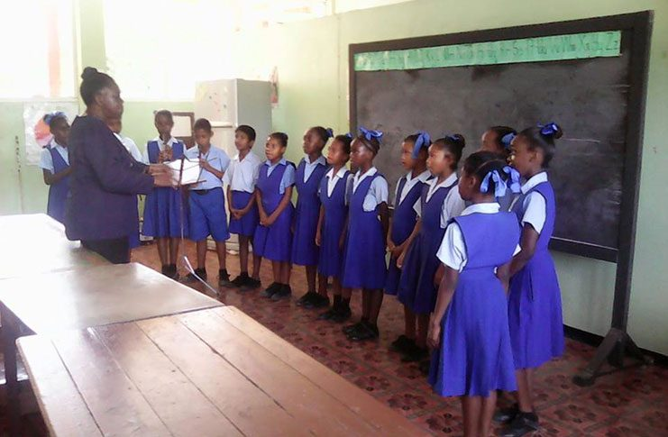 Head Teacher Miss Carmen Cox conducting music to her students