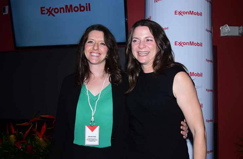 Incoming Senior Director (ExxonMobil), Deebra Moe, standing with the Outgoing Senior Director (ExxonMobil) Kimberly Brassington (Adrian Narine photo)