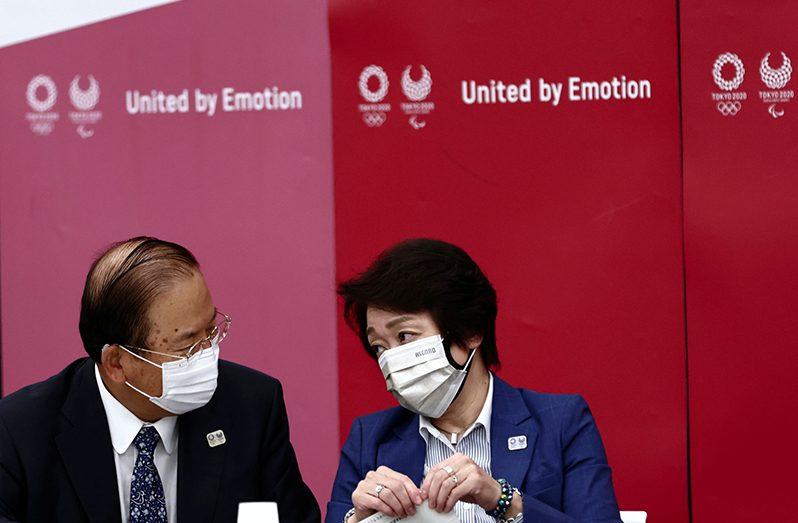Tokyo 2020 Olympics organising committee president Seiko Hashimoto and Tokyo organising committee CEO Toshiro Muto chat before the start of the Tokyo 2020 Olympics executive board meeting in Tokyo, Japan June 8, 2021. (Behrouz Mehri/Pool via REUTERS)