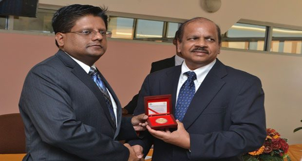 Finance Minister Dr. Ashni Singh receives a copy of the commemorative coin from Bank of Guyana Governor Dr Gobind Ganga