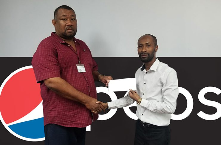 DDL Marketing Executive Larry Wills (right) hands over sponsorship to RHTYSC Secretary/CEO Hilbert Foster.