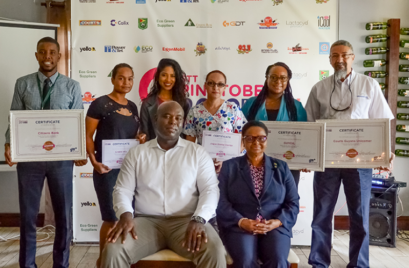 GTT CEO, Justin Need (seated) and Public Health Minister, Volda Lawrence, with representatives from some of the major companies that sponsored Pinktober 2019