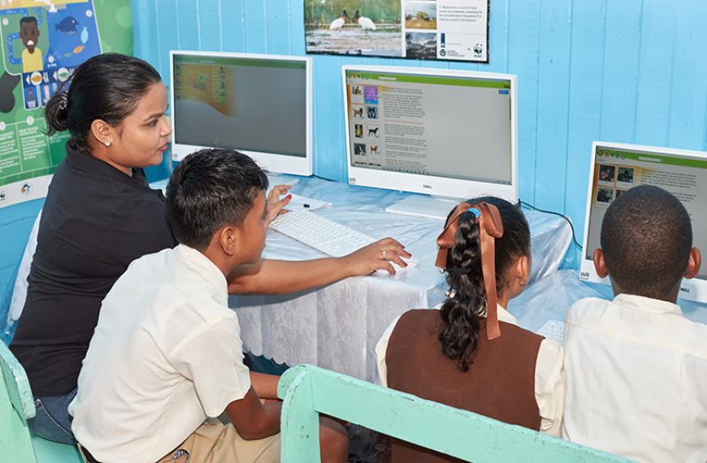 At left: Pomeroon Trading's Community Development Coordinator, Tana Yussuff, in the new library and computer centre with pupils operating the computers