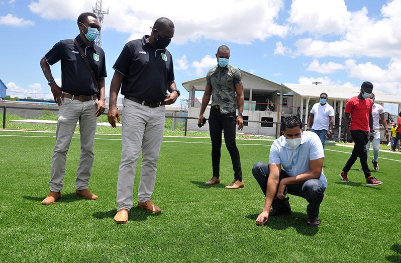 GFF president Wayne Forde (2nd left) observes as Minister Ramson gets a feel of the turf at the GFF National Training Facility. (GFF photo)