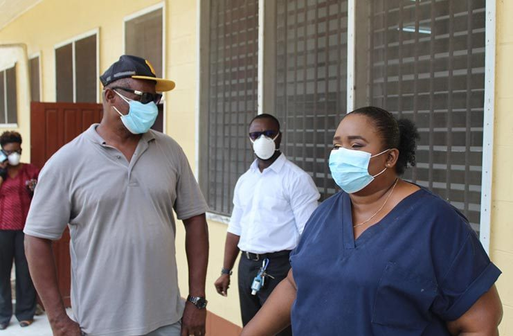 Regional Executive Officer, Orrin Gordon, in deep conversation with Dr Tracey Bovell, Emergency Medicine Specialist at GPHC, while Medical Superintendent at Linden Hospital Complex, Dr Joseph London, pays rap attention as they tour the isolation facility at Wismar hospital.