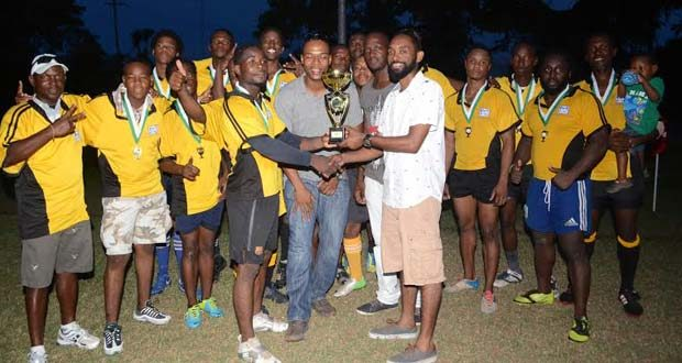 Golden Brook representative Dustani Barrow presents the winner's trophy to Yamaha Caribs Captain Akeem Fraser, while other sponsors and players look on. Photo Name: Rugby Presentation