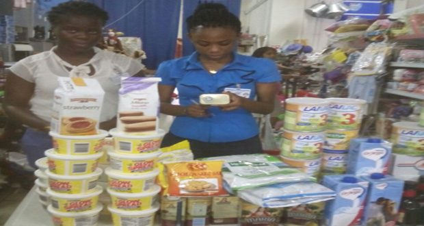 Two GAD staffers with some of the expired foodstuff  that were seized and destroyed