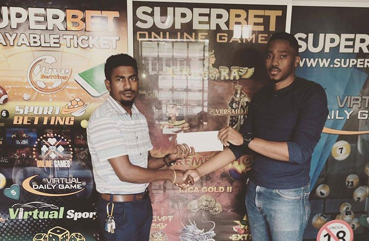Dwight Dodson (left) collects a cheque from a Superbet Guyana representative.