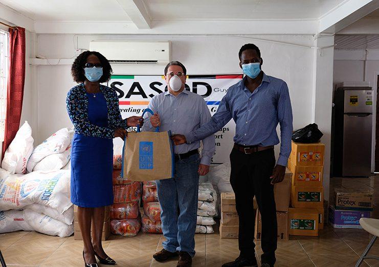 UNDP Resident Representative, Jairo Valverde hands over food items to National AIDS Programme Secretariat Director, Dr. Rhonda Moore and SASOD Managing Director, Joel Simpson
