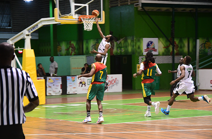 Guyana's Travis Belgrave scores at the rim during his team's 90-73 points win over Grenada in their Three-game Goodwill Series at Cliff Anderson Sports Hall. (Adrian Narine photo)