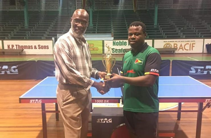 Orin Hickerson (right) collects the championship trophy from chairman of the Forbes Burnham Foundation, Vincent Alexander.