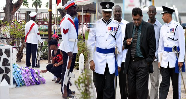 Commissioner of Police Seelall Persaud and Public Security Minister Khemraj Ramjattan in discussion shortly after the minister arrived for the ceremony. At right, a relative lays a wreath in rememberance of her hero