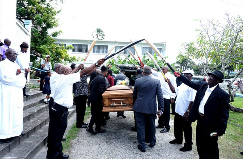 Paul bearers which included some national cricketers guide the casket of the late Basil Butcher to the hearse as with cricket bats forming an arch (Carl Croker Photo)