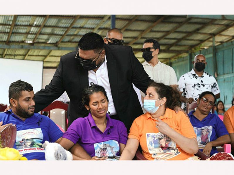 President, Dr. Irfaan Ali comforts the family of young Aiden Kiritpal (Office of the President photo)