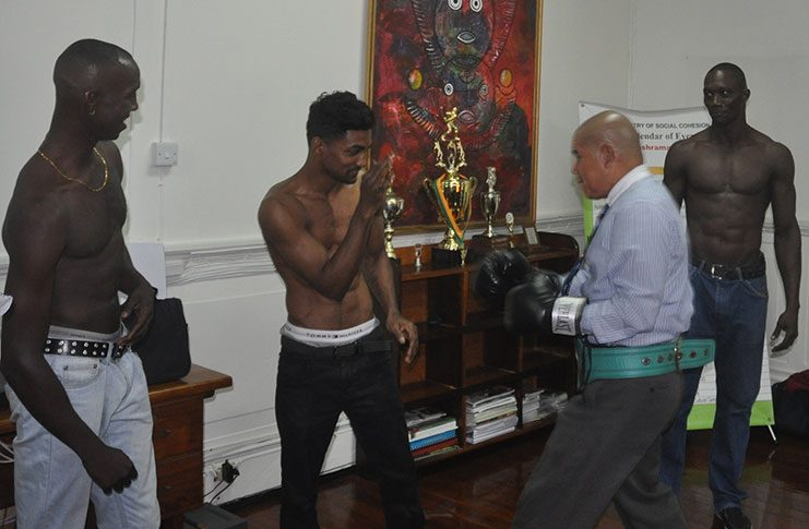 Minister of Sport Dr George Norton (2nd right) engages Guyana's WBC CABOFE and International Continental bantamweight champion Elton `The Bully' Dharry in a sparring session prior to yesterday's press conference at the Minister's Main Street office in the presence of Dexter `Cobra' Gonsalves (extreme left) and Shawn Corbin (extreme right).