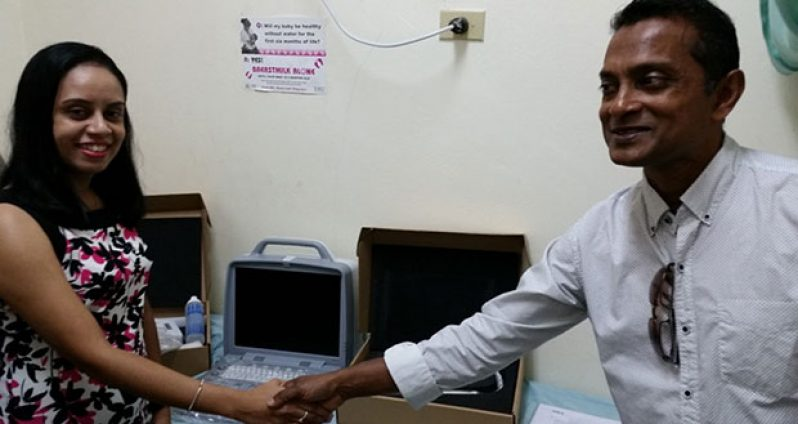 Dr. Alesha Bulkan, ultrasound specialist at the Mahaicony Hospital, receiving the modern ultrasound equipment from Chief Operations Officer of the GMR, Sharir Chan