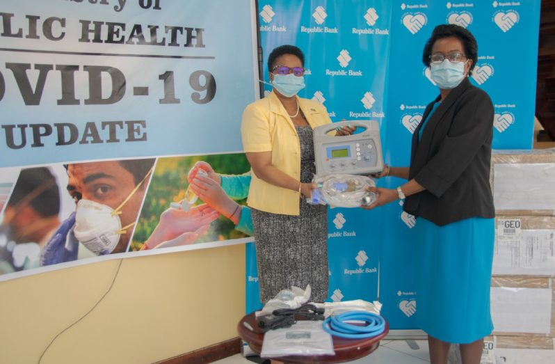 Republic Bank Representative, Denise Hobbs (right) hands over the bank's donation of portable ventilators to Minister of Public Health, Volda Lawrence