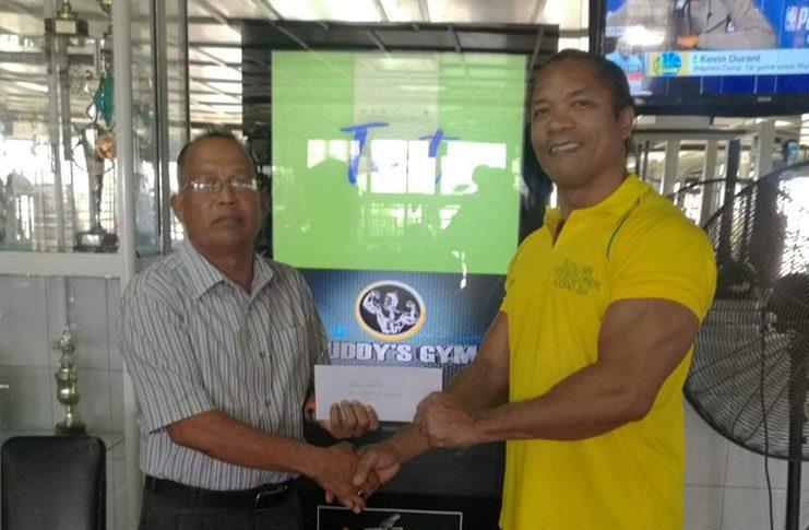 GAPLF committee member, Martin Webster (left) receives the sponsorship package from Buddy's Gym Manager, Mr Crush Pharbo.